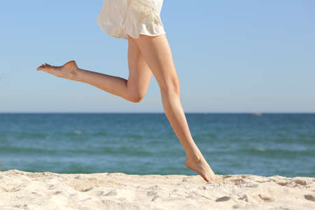 Foto de Beautiful woman long legs jumping on the beach with the sea in the background                  - Imagen libre de derechos