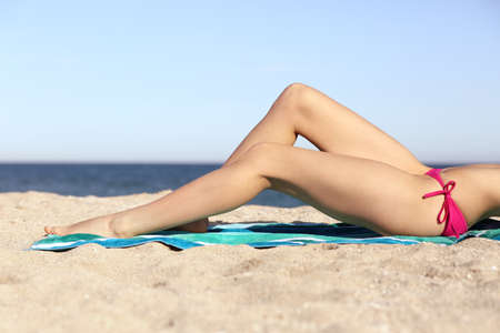 Photo pour Beauty perfect woman waxing legs sunbathing on the sand of the beach with horizon in the background                  - image libre de droit