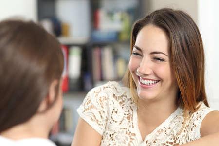 Foto de Happy woman taking a conversation and laughing with a friend at home            - Imagen libre de derechos