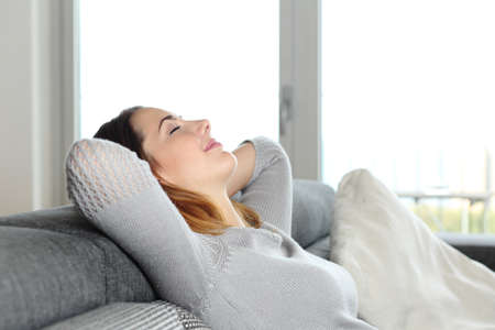 Photo pour Happy relaxed woman resting on a couch at home with arms in the head - image libre de droit