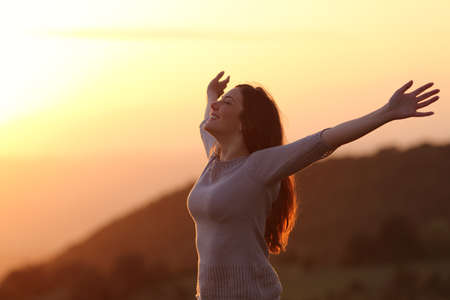 Foto de Backlit of  a woman at sunset breathing fresh air raising arms  - Imagen libre de derechos