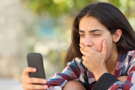 Photo pour Worried teenager girl looking at her smart phone in a park with an unfocused background - image libre de droit