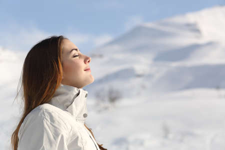 Profile of an explorer woman breathing fresh air in winter with a snowy mountain in the background