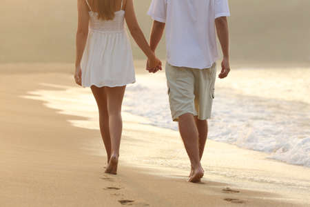 Photo pour Back view of a couple taking a walk holding hands on the beach at sunrise - image libre de droit