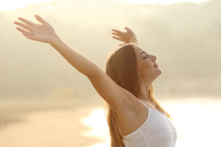 Photo for Relaxed woman breathing fresh air raising arms at sunrise with a warmth golden background - Royalty Free Image