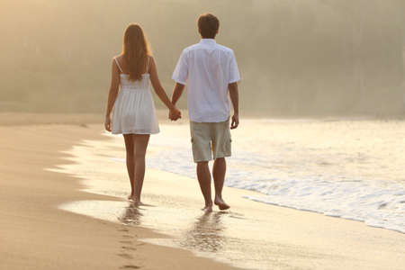 Photo pour Back view of a couple walking and holding hands on the sand of a beach at sunset - image libre de droit