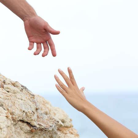 Foto de Man and woman hands helping concept with the sea in the background - Imagen libre de derechos