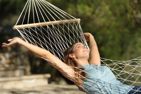 Foto de Happy woman relaxing on a hammock on holidays and raising arms in the mountain - Imagen libre de derechos