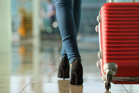 Foto de Traveler woman legs walking carrying a suitcase in an airport - Imagen libre de derechos