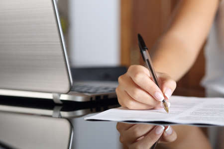 Photo pour Close up of a woman hand writing a contract with a laptop beside at home or office - image libre de droit