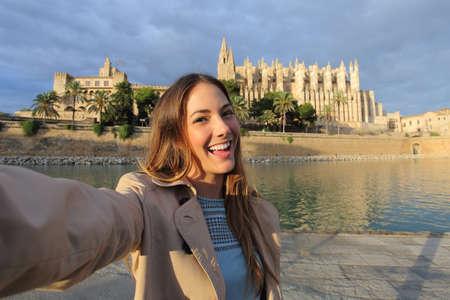 Photo pour Tourist woman photographing a selfie in Palma de Mallorca Cathedral on holidays - image libre de droit