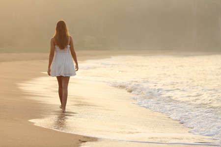 Photo pour Back view of a woman walking on the sand of the beach at sunset - image libre de droit