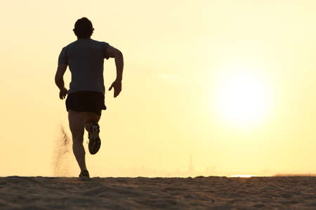 Photo pour Back view silhouette of a runner man running on the beach at sunset with sun in the background - image libre de droit