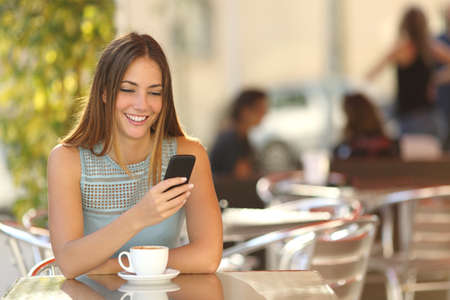 Foto de Girl texting on the smart phone in a restaurant terrace with an unfocused background - Imagen libre de derechos