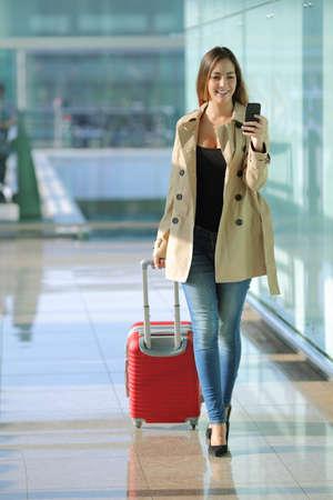 Foto de Front view of a traveler woman walking and using a smart phone in an airport corridor - Imagen libre de derechos
