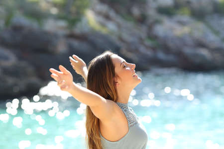 Photo for Happy woman breathing fresh air raising arms on holidays with a tropical sea in the background - Royalty Free Image