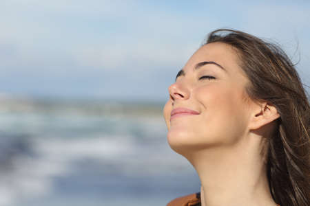 Foto de Closeup portrait of a relaxed woman breathing fresh air on the beach - Imagen libre de derechos