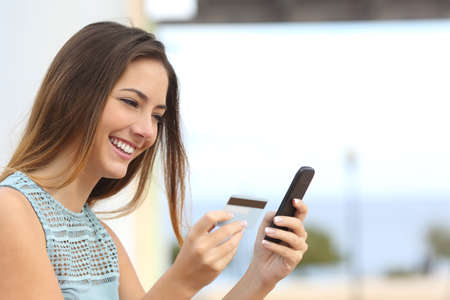 Photo pour Portrait of a happy woman buying online with a smart phone outdoors - image libre de droit
