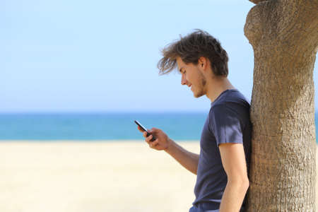 Photo pour Side view of an attractive man using a smart phone on the beach with the sea and horizon in the background - image libre de droit