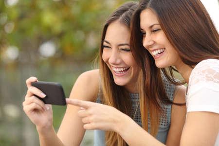 Foto de Two funny women friends laughing and sharing social media videos in a smart phone outdoors - Imagen libre de derechos