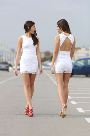Photo pour Two women walking on the street with the same dress looking each other with hate - image libre de droit