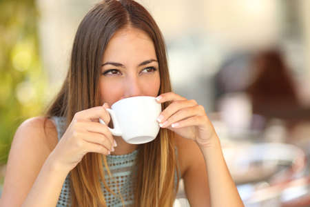 Photo for Woman drinking a coffee from a cup in a restaurant terrace while thinking and looking sideways - Royalty Free Image