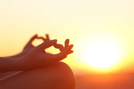 Photo for Back light of a woman hands exercising yoga at sunset with a warmth background - Royalty Free Image