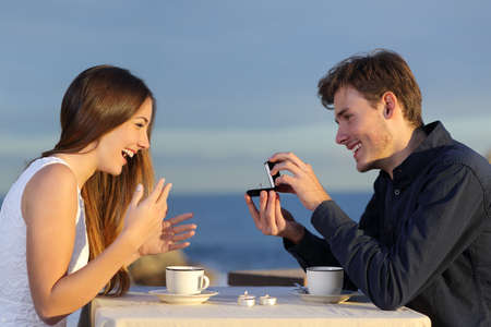 Foto de Boyfriend requesting hand of his girlfriend with a engagement ring in a restaurant with the ocean in the background - Imagen libre de derechos