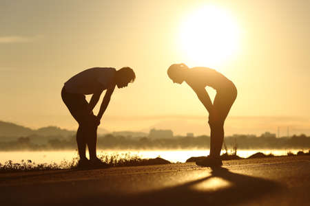 Foto de Side view of a exhausted and tired fitness couple silhouettes at sunset - Imagen libre de derechos