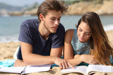 Teenager couple or friends students studying on the beach learning together