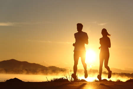 Photo pour Silhouette of a couple running at sunset with the sun in the background - image libre de droit