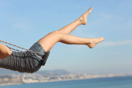 Foto de Hair removed woman legs swinging on the beach with the sky in the background - Imagen libre de derechos