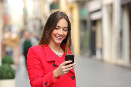 Foto de Girl walking and texting on the smart phone in the street wearing a red jacket in winter - Imagen libre de derechos