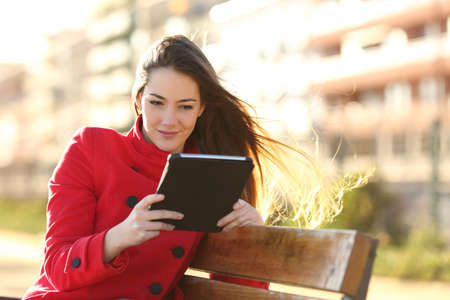 Photo pour Woman reading an ebook or tablet in an urban park with buildings in the background - image libre de droit