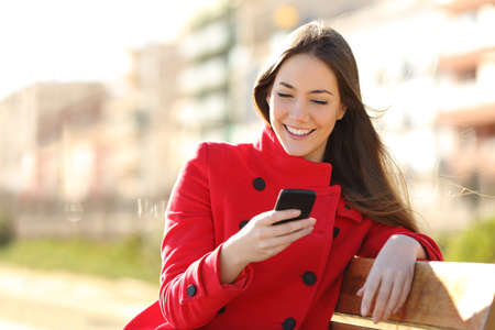 Foto de Girl texting on the smart phone sitting in a park wearing a red jacket and sitting in a bench in a park - Imagen libre de derechos