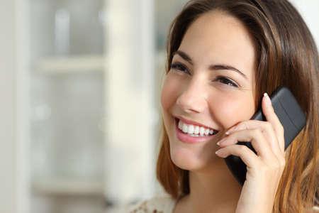 Photo pour Close up portrait of a happy woman talking on the mobile phone at home - image libre de droit