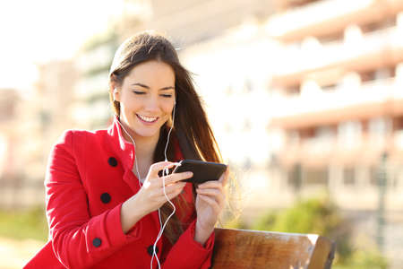 Foto de Woman watching videos in a smart phone with earphones sitting in a park with an unfocused buildings in the background - Imagen libre de derechos