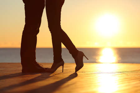 Photo pour Couple legs silhouette falling in love hugging at sunset on the beach with the sun in the background - image libre de droit
