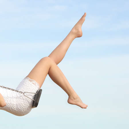 Foto de Perfect woman waxing hair removal legs swinging with the blue sky in the background - Imagen libre de derechos