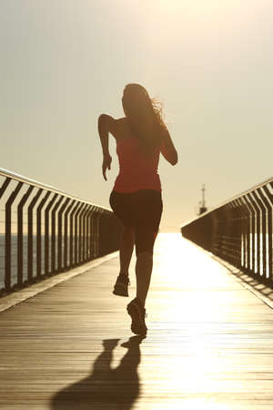 Photo pour Back view of a runner silhouette running fast at sunset on a bridge on the beach - image libre de droit