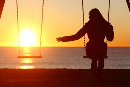 Photo pour Single or divorced woman alone missing a boyfriend while swinging on the beach at sunset - image libre de droit