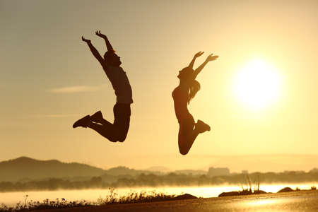 Foto de Fitness couple jumping happy at sunset with the sun in the background - Imagen libre de derechos