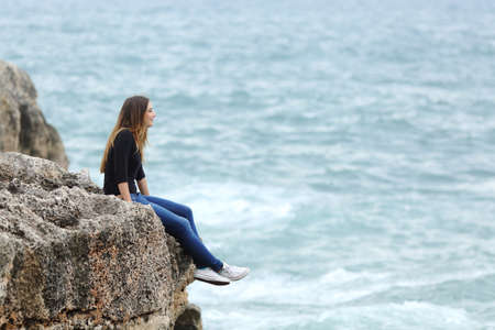 Side view of a full body of a casual woman thinking sitting in a cliff watching the sea
