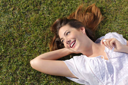 Photo for Top view of a happy relaxed woman lying on the green grass and looking at side smiling - Royalty Free Image