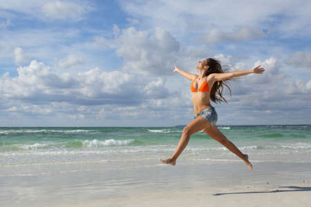 Foto de Happy woman jumping and running on the beach on holidays with a cloudy sky in the background - Imagen libre de derechos