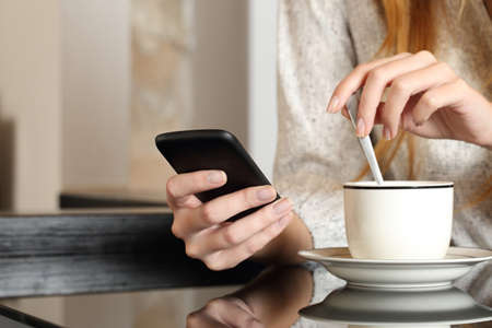Photo pour Woman hand using a smart phone during breakfast at home while is preparing a coffee cup - image libre de droit