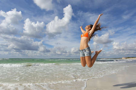 Foto de Happy girl wearing bikini jumping on the beach on holidays with a cloudy sky in the background - Imagen libre de derechos