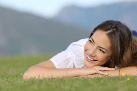 Pretty happy woman thinking on the grass and looking at side in the mountain