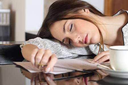 Photo pour Tired overworked woman resting while she was working writing notes - image libre de droit