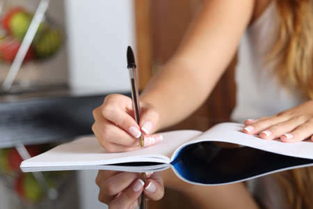 Foto de Close up of a woman writer hand writing in a notebook at home in the kitchen - Imagen libre de derechos